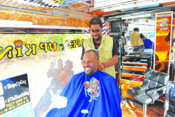 """Emmanuel """"E-Man"""" Azoro, also known as the """"Shape-Up King"""" — a charismatic, part-salesman, full-time barber — has emerged as the owner of one of the first mobile barbershops in the nation's capital. (Robert Eubanks/District Chronicles)"""
