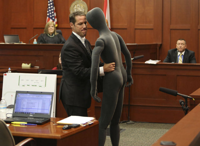 Assistant State Attorney John Guy uses a foam dummy to describe the altercation between George Zimmerman and Trayvon Martin to defense witness and law enforcement expert Dennis Root. Gary W. Green / MCT