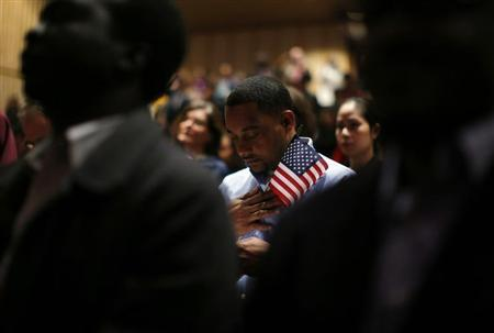 Immigrants stand for the invocation during a naturalization ceremony to become new U.S. citizens at Boston College in Chestnut Hill