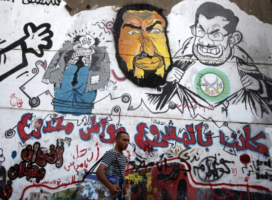 Amr Abdallah Dalsh/Reuters -  A man walks past graffiti depicting ousted Egyptian President Mohamed Morsi and others in downtown Cairo on Sept. 24.