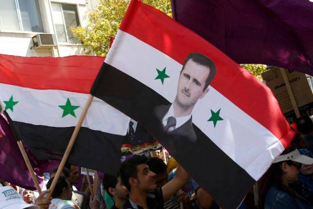 Supporters of Syria President Bashar al-Assad wave a Syrian national flag.