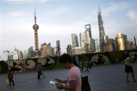 A man checks his iPad on the Bund in front of the financial district in Shanghai