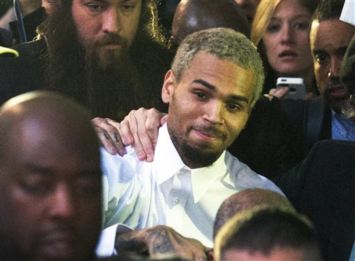 "In this Monday, Oct. 28, 2013 file photo, singer Chris Brown, center, departs the H. Carl Moultriel courthouse after he was released from jail following his arrest for allegedly punching another man, in Washington. A representative for the R&B star announced Tuesday, Oct. 29, 2013 that Brown has decided to go to rehab to ""gain focus and insight into his past and recent behavior, enabling him to continue the pursuit of his life and his career from a healthier vantage point."" (AP Photo/Cliff Owen, File)"