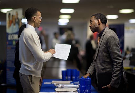 In this Thursday, Nov. 14, 2013, file photo, retired U.S. Air Force Master Sgt. Thomas Gipson, of Atlanta, right, has his resume looked over by Ralph Brown, a management and program analyst with the Centers for Disease Control and Prevention, during a job fair for veterans at the VFW Post 2681, in Marietta, Ga. The government reports on job openings and labor turnover for September on Friday, Nov. 22, 2013. (AP Photo/David Goldman, file)