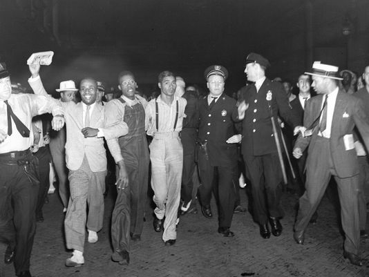 "n this July 26, 1937 file photo, police escort two of the five recently freed ""Scottsboro Boys,"" Olen Montgomery, wearing glasses, third left, and Eugene Williams, wearing suspenders, fourth left, through the crowd greeting them upon their arrival at Penn Station in New York. In a final chapter to one of the most important civil rights episodes in American history, Alabama lawmakers voted Thursday, April 4, 2013, to give posthumous pardons to the nine black teens who were wrongly convicted of raping two white women in 1931. (Photo: Associated Press)"