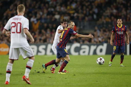 Barcelona's Andres Iniesta, centre, vies for the ball with AC Milan's Riccardo Montolivo during a group H Champions League soccer match at the Camp Nou stadium, in Barcelona, Spain, Wednesday Nov. 6, 2013. (AP Photo/Emilio Morenatti)