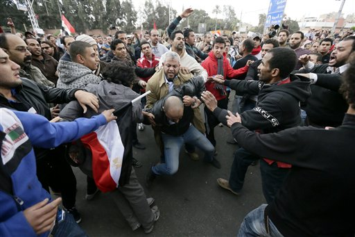 In this Wednesday, Dec. 5, 2012 file photo. supporters of then- Egyptian President Mohammed Morsi's beat an opponent, center, during clashes outside the presidential palace, in Cairo, Egypt. Egyptian authorities switched the venue for the trial of the former Islamist president on Sunday, Nov. 3, 2013 a last-minute change made after the Muslim Brotherhood called for mass demonstrations at the original location. The trial of Morsi, now to be held east of the capital on Monday, could lead to another round of bloodshed as his supporters look likely to face an emboldened security apparatus that has boosted its forces for the hearing. (AP Photo/Hassan Ammar, File)