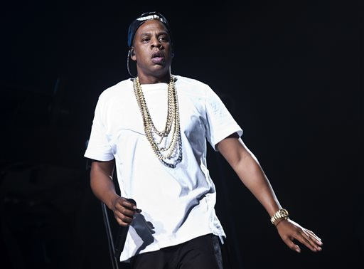 FILE - In this Oct. 10, 2013 file photo, U.S singer Jay Z performs on stage at the o2 arena in east London, as part of his Magna Carta World Tour. The rapper says he'll continue his collaboration with Barneys despite allegations that black shoppers were racially profiled at the high-end retailer. Jay Z said in a statement Friday, Nov. 15, 2013, that he's agreed to move forward with next week's launch of his BNY SCC collection under the condition he helps lead the store's review of its policies. He says he's in a unique position to effect change. (Photo by Joel Ryan/Invision/AP, File)