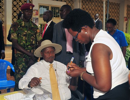 Uganda President Yoweri Museveni, center seated, takes an HIV/AIDS test at Kiswa Health Centre in the capital Kampala, Friday Oct. 8,  2013. The president and the first lady test for HIV in public, a rare event for public leaders in the East African country that once was a leader in efforts to fight AIDS but which in recent times has been said to lag behind other African countries. (AP Photo / Stephen Wandera).