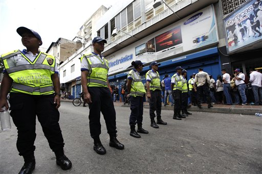 Venezuelan National Police stand guard outside an appliance store in Caracas, Venezuela, Wednesday, Nov. 13, 2013.  President Nicolas Maduro in recent days ordered the military to take over appliance stores, slashing prices, leading bargain hunters to form block-long lines across the country. The populist measures seem designed to help Maduro's party get over the hump of next month's mayoral vote, its first electoral test since the president narrowly defeated opposition leader Henrique Capriles in April. But while the measures apparently are popular with voters, Maduro runs the risk of cannibalizing an already damaged economy. (AP Photo/Ariana Cubillos)