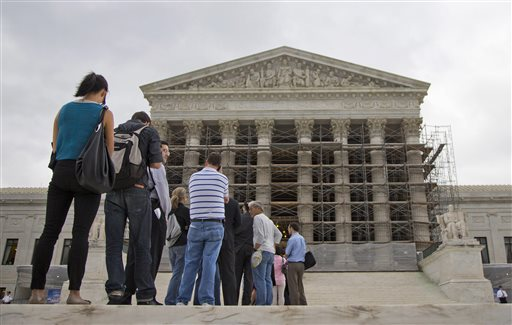 This Oct. 7, 2013 file photo shows people wait in line to enter the Supreme Court in Washington. The Supreme Court asks God for help before every public session. Now the justices will settle a dispute over prayers in the halls of government. The case before the court involves prayers said at the start of town council meetings in Greece, N.Y., outside of Rochester. It is the court's first legislative prayer case since 1983, when the justices said that an opening prayer is part of the nation's fabric and not a violation of the First Amendment. The federal appeals court in New York held that the town violated the Constitution by opening nearly every meeting over an 11-year span with prayers that stressed Christianity. (AP Photo/ Evan Vucci, File)