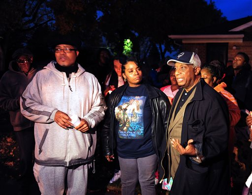 In this Wednesday, Nov. 6, 2013 photo, from left, Pastor W. J. Rideout, Renisha McBride's aunt Bernita Spinks and Ron Scott speak to the media during a vigil  in Dearborn Heights, Mich., for Renisha McBride in the front of the home where she shot early Saturday.  No charges have been filed after authorities said McBride, of Detroit, was killed by a shotgun blast to the face early Saturday in Dearborn Heights. According to police, the homeowner told investigators that he thought someone was trying to break into his home and accidentally discharged the gun. (AP Photo/Detroit News, Ricardo Thomas)