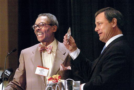 In this May 18, 2006, file photo, Robert M. Bell, left, Chief Judge of the Maryland Court of Appeals, presents U.S. Supreme Court Chief Justice John Roberts with a Maryland flag bowtie at the Maryland Judicial Conference in Cambridge, Md. Bell was 16 years old when he recruited classmates to join a sit-in at a downtown Baltimore restaurant. Twelve demonstrators, including Bell, were charged 50 years ago this month with trespassing in a civil rights case that eventually made it all the way to the U.S. Supreme Court. In the 50 years since Bell v Maryland, Bell, now retired, went on to become a lawyer and later a judge on Maryland's highest court, where he sat on the bench with two men who had been prosecutors on his case. (AP Photo/The Star Democrat, Chris Polk, File)