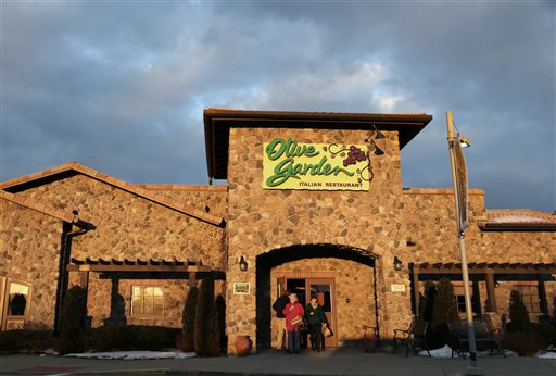 In this Wednesday, March 20, 2013 file photo, people leave an Olive Garden restaurant at sunset in Foxborough, Mass. Darden Restaurants Inc. reports quarterly financial results before the market open on Thursday, Dec. 19, 2013. (AP Photo/Steven Senne, File)