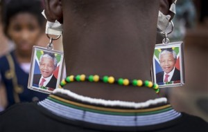 A man wears keyrings showing the face of Nelson Mandela taped to his ears to mimic earrings as he and others celebrate his life, in the street outside his old house in Soweto, Johannesburg, South Africa Friday, Dec. 6, 2013.