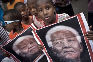 South African children hold placards showing the face of Nelson Mandela as they celebrate his life.