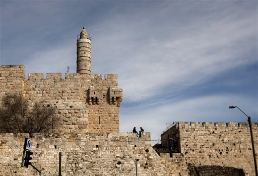 In this March 7, 2012 file photo, a couple sits next to the Tower of David on the wall surrounding Jerusalem's old city. (AP Photo/Sebastian Scheiner, File)