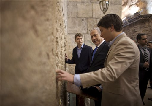 In this Jan. 22, 2013 file photo, Israeli Prime Minister Benjamin Netanyahu, center, prays with his sons Yair, background, and Avner, right,  at the Western Wall, the holiest site where Jews can pray, in Jerusalem's Old City. (AP Photo/Uriel Sinai, Pool, File)