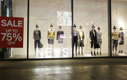 Mannequins display fashions in an H&M storefront window advertising discounts up to 75%, Tuesday, Jan. 14, 2014 in New York. (AP Photo/Mark Lennihan)
