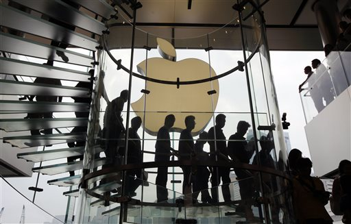 In this Sept. 24, 2011, file photo, customers walk past a huge Apple logo at the new store which is located on two floors linked by a glass spiral staircase in Hong Kong's upscale International Financial Center Mall. Friday, January 24, 2014, marks thirty years after the first Mac computer was introduced, sparking a revolution in computing and in publishing as people began creating fancy newsletters, brochures and other publications from their desktops. (AP Photo/Kin Cheung)