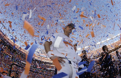 Denver Broncos quarterback Peyton Manning is engulfed in confetti during the trophy ceremony after the AFC Championship NFL playoff football game in Denver, Sunday, Jan. 19, 2014. The Broncos defeated the Patriots 26-16 to advance to the Super Bowl. (AP Photo/Charlie Riedel)