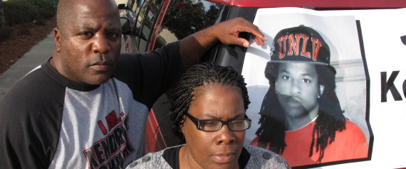 Kenneth and Jacquelyn Johnson stand next to a banner on their SUV showing their late son, Kendrick Johnson, on Dec. 13, 2013, in Valdosta, Ga. The 17 year old was found dead inside a rolled up gym mat at his high school Jan. 11, 2013, and authorities ruled it was a freak accident. Kendrick's family believes someone killed him and has been fighting to reopen the case. (AP Photo/Russ Bynum) | ASSOCIATED PRESS