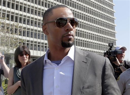 In this Feb. 14, 2014, photo, former NFL safety Darren Sharper leaves a courthouse in Los Angeles. An arrest warrant has been issued for Sharper and another man, accusing them of raping two women in New Orleans last year. (AP Photo/Nick Ut )