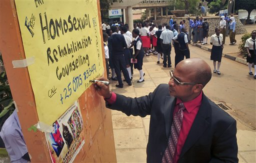 "Ugandan anti-gay activist Pastor Martin Ssempa posts up a public notice offering ""rehabilitation"" for homosexuals at Uganda's National Theatre in Kampala, Uganda Tuesday, Feb. 25, 2014. (AP Photo/Stephen Wandera)"