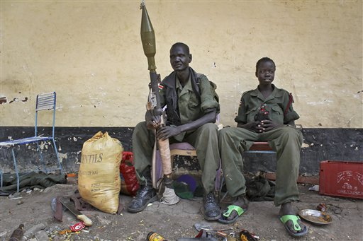 In this photo taken Wednesday, Feb. 26, 2014, rebels sit in the now-emptied hospital in Malakal, South Sudan. (AP Photo/Ilya Gridneff)