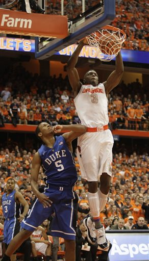 Syracuse's Jerami Grant, right, jams the ball for two points against Duke''s Rodney Hood, left, in overtime of an NCAA college basketball game in Syracuse, N.Y., Saturday, Feb. 1, 2014. Syracuse won 91-89. (AP Photo/Nick Lisi)