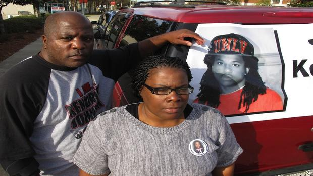 Kenneth and Jacquelyn Johnson stand next to a banner on their SUV showing their late son, Kendrick Johnson, on Dec. 13, 2013, in Valdosta, Ga.  (AP PHOTO/RUSS BYNUM)
