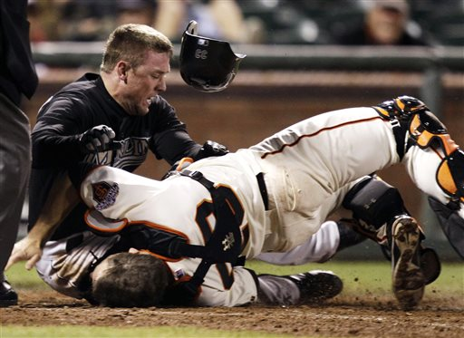 In this May 25, 2011 file photo, Florida Marlins' Scott Cousins, top, collides with San Francisco Giants catcher Buster Posey (28) on a fly ball from Emilio Bonifacio during the 12th inning of a baseball game in San Francisco. (AP Photo/Marcio Jose Sanchez, File)
