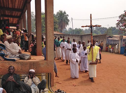 In this photo taken on Sunday, Feb. 23, 2014, Muslim men, left, seeking refuge in a Catholic church, look on as a Catholic church service takes place in Carnot a town 200 kilometers (125 miles) from the Cameroonian border, in, Central African Republic. The Christian militiamen knew hundreds of Muslims were hiding at the Catholic church and came with their ultimatum: Evict the families to face certain death or else the entire place would be burned to the ground.  (AP Photo/Krista Larson)