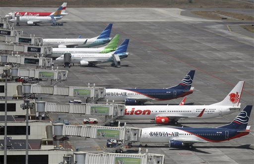 In this Sept. 25, 2012 file photo, budget airlines' passenger jets, Malaysia's AirAsia, top, Indonesia's Badavia Air, third from bottom, and Indonesia's Lion Air, second bottom, are parked on the tarmac with Indonesian planes of domestic airline Merpati Nusantara, second top, and the flagship carrier Garuda Indonesia at Juanda International Airport in Surabaya, East Java, Indonesia. (AP Photo/Trisnadi, File)