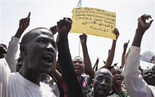 "A group of South Sudanese chant at a demonstration held in support of President Salva Kiir and against ""foreign encroachment"" in Juba, South Sudan Monday, March 10, 2014. Arabic on placard reads ""No foreigners are allowed to intervene"". (AP Photo/Mackenzie Knowles-Coursin)"