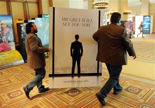 """Sheldon Domke, left, and Adam Mast move an advertisement for the upcoming film """"Fifty Shades of Grey"""" during the second day of  CinemaCon 2014 on Tuesday, March 25, 2014 in Las Vegas. The film is set for release Valentine's Day of 2015. (Photo by Chris Pizzello/Invision/AP)"""