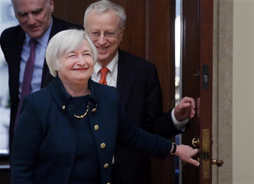 In this Monday, Feb. 3, 2014, file photo, Janet Yellen, followed by her husband, Nobel Prize winning economist George Akerlof, smiles as she walks into a room of applause by staff members before she is administered the oath of office as Federal Reserve Board chair, at the Federal Reserve in Washington. Yellen is the first woman to lead the Federal Reserve. (AP Photo/Charles Dharapak, File)