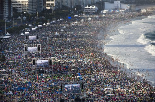 In this file photo taken on July 27, 2013, pilgrims and residents gather on Copacabana beach before the arrival of Pope Francis for World Youth Day in Rio de Janeiro, Brazil.  (AP Photo/Felipe Dana)