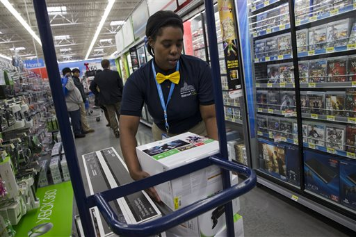 In this Wednesday, Dec. 4, 2013, file photo, Tracey Anderson, 26, re-stocks X-Box sets on opening day of a new Wal-Mart on Georgia Avenue Northwest in Washington. (AP Photo/Jacquelyn Martin, File)