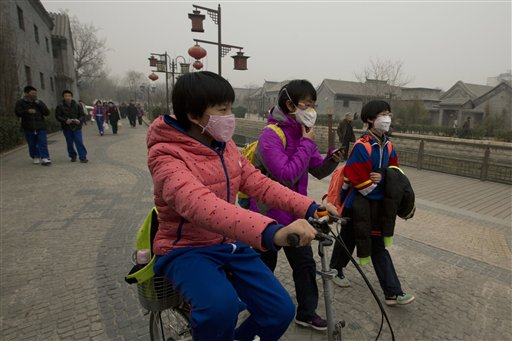 In this Tuesday, Feb. 25, 2014 file photo, children wearing masks walk home after school in Beijing, China. Air pollution kills about 7 million people worldwide every year according to a new report from the World Health Organization published Tuesday, March 25, 2014. The agency said air pollution triggers about 1 in 8 deaths and has now become the single biggest environmental health risk, ahead of other dangers like second-hand smoke. (AP Photo/Ng Han Guan, File)