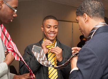"Fonzworth Bentley teaches students the proper way to tie a Windsor knot at the ""Tied to Greatness"" workshop during the UNCF Empower Me Tour presented by Wells Fargo in Charlotte, NC."