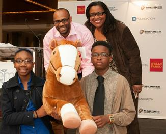 "Wells Fargo leaders Dewey Norwood and Georgette ""Gigi"" Dixon photographed with two Charlotte students who received Mack, Wells Fargo's commemorative 16oth anniversary pony during the UNCF Empower Me Tour."