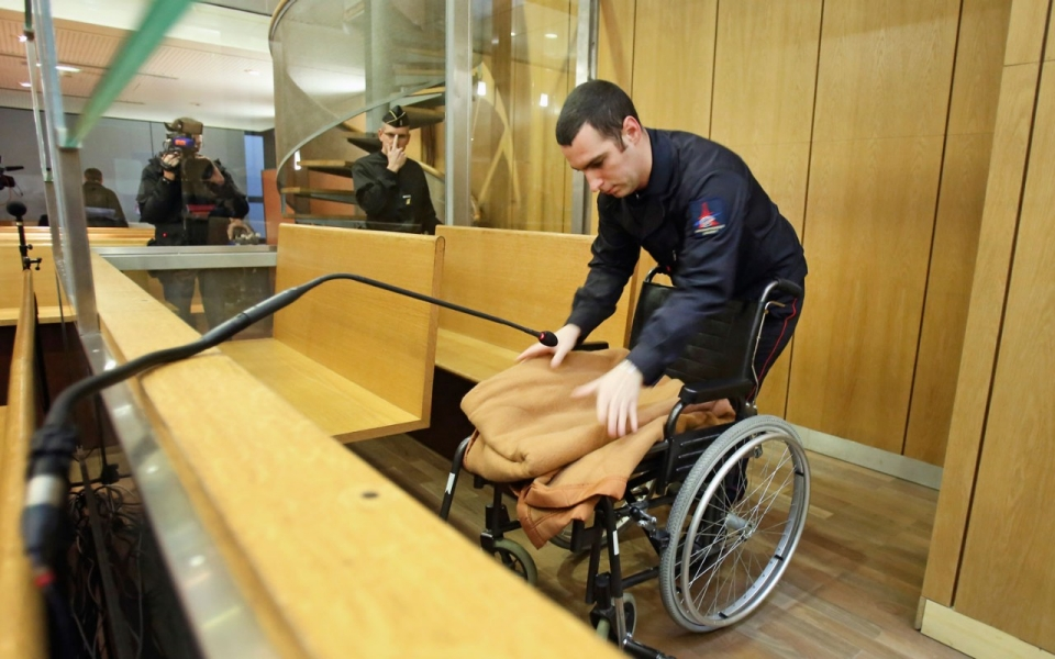 A man prepares the courtroom with the wheelchair of Pascal Simbikangwa, a 54-year-old former Hutu intelligence chief, who faces charges of complicity in genocide. (AP Photo/Remy de la Mauviniere)