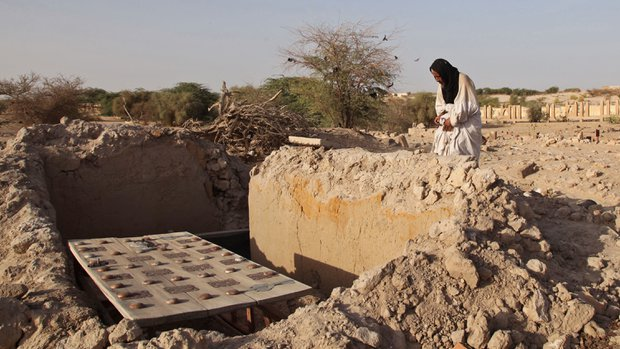 In this photo taken on Friday, April 4, 2014, Mohamed Maouloud Ould Mohamed, the care taker of the tomb's at the Timbuktu's mausoleums pray at a damaged tomb's in Timbuktu, Mali. Masons working to restore Timbuktu's storied mausoleums are worried that the coming rains could wreak even more damage on the buildings, many of which are barely more than a heap of mud bricks following attacks by the Islamist radicals who overran northern Mali. (AP Photo/Baba Ahmed)