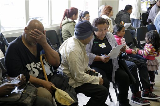 This March 31, 2014 file photo shows applicants waiting to be called during a health care enrollment event at the Bay Area Rescue Mission in Richmond, Calif. (AP Photo/Eric Risberg, File)