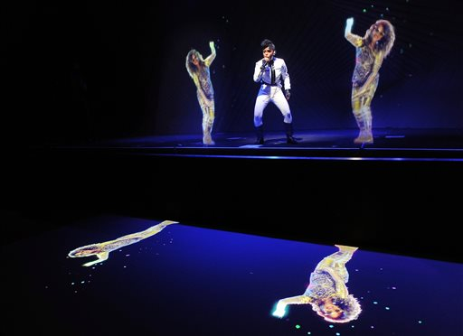 Janelle Monae, center, performs alongside holograms of M.I.A. during a launch party for the Audi M3 on Thursday, April 3, 2014 in West Hollywood, Calif. (Photo by Chris Pizzello/Invision/AP)