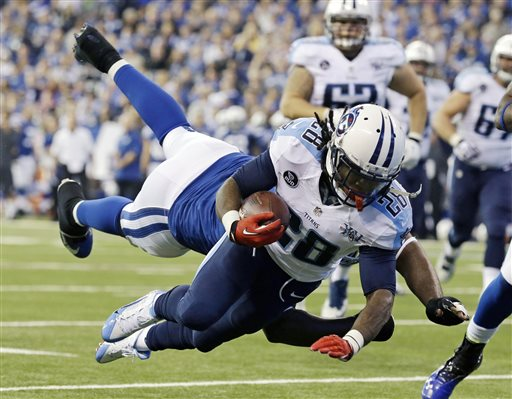 In this Dec. 1, 2013 file photo, Tennessee Titans' Chris Johnson (28) dives while being tackled by Indianapolis Colts' Cory Redding during the first half of an NFL football game in Indianapolis. (AP Photo/Michael Conroy, File)