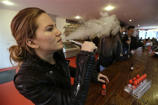In this Feb. 20, 2014 photo, Talia Eisenberg, co-founder of the Henley Vaporium, uses her vaping device in New York. Under a New York City law taking effect Tuesday, April 29, 2014, vaporizing devices will be treated the same as a tobacco-based cigarette. (AP Photo/Frank Franklin II, File)