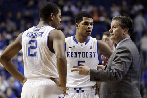 In this Jan. 21, 2014 file photo, Kentucky head coach John Calipari, right, instructs Aaron Harrison (2) and Andrew Harrison (5) during the second half of an NCAA college basketball game in Lexington, Ky. The Kentucky twin freshman guards will return for a second season to a stocked Wildcats squad coming off an NCAA championship appearance. (AP Photo/James Crisp, File)