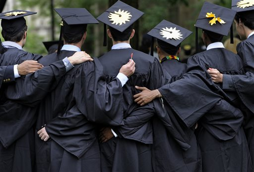In this May 20, 2013 file photo, graduates pose for photographs during commencement at Yale University in New Haven, Conn.  The job market for new college graduates is brightening but remains weaker than before the Great Recession began. (AP Photo/Jessica Hill, File)